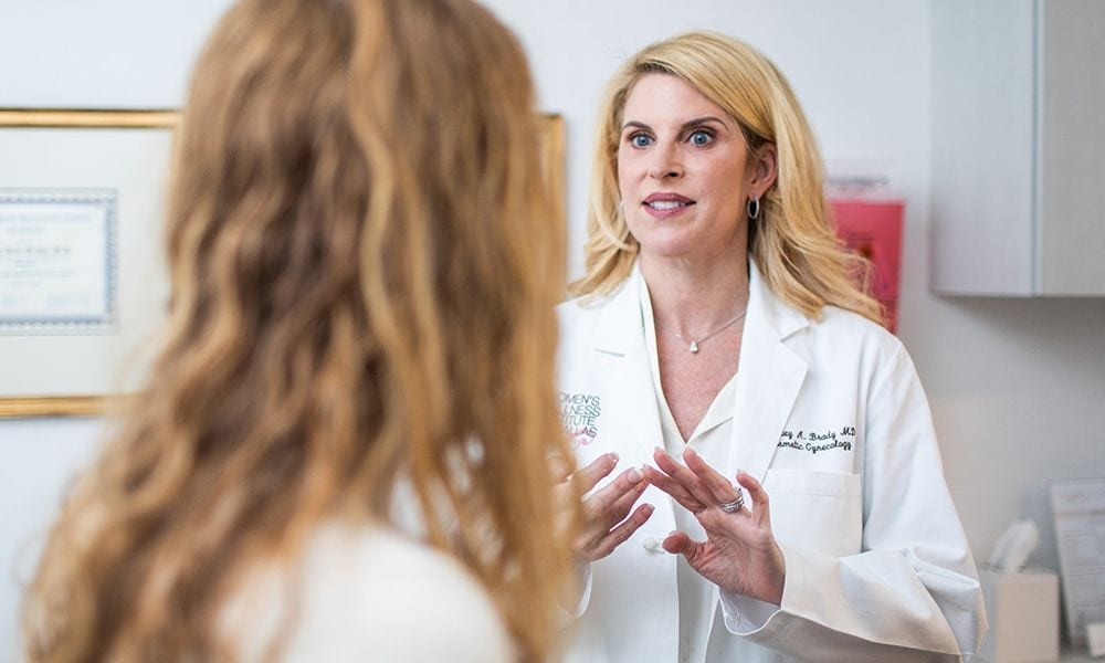 Dr. Brady in a Lab Coat Speaking with a Female Patient