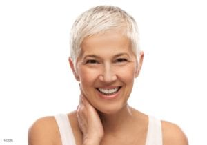 Mature Female with short white hair and white top smiling